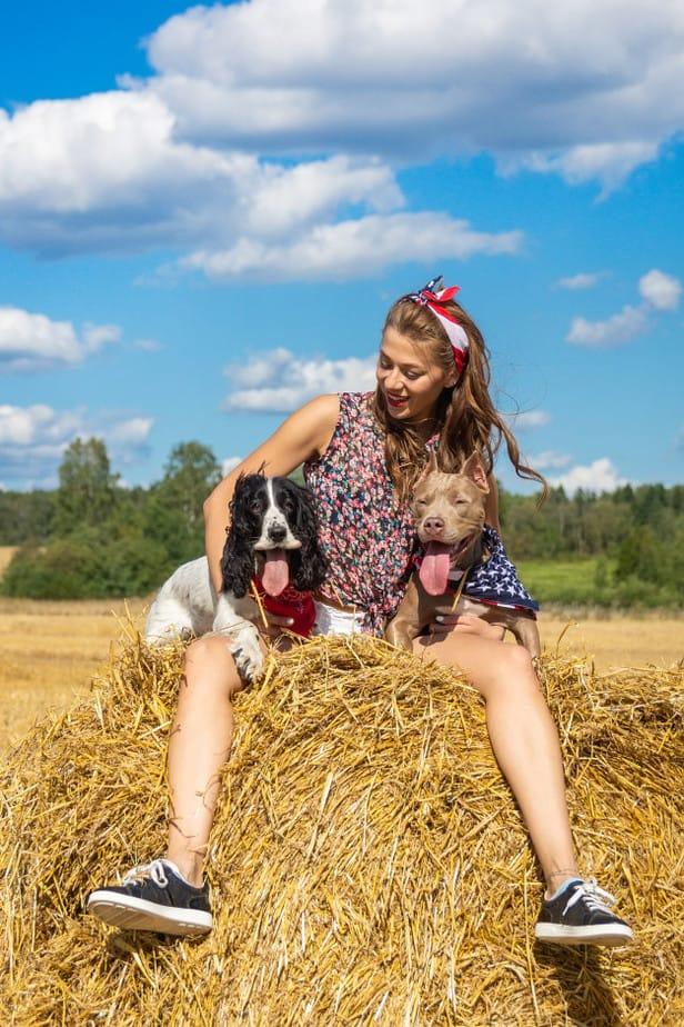Uma menina sentada em cima da palha segurando dois cachorros