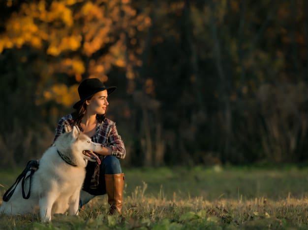 Husky Siberiano e uma mulher sentados na grama