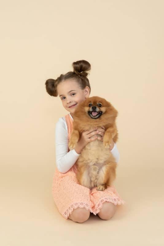 Menina segurando o cachorro em fundo rosa