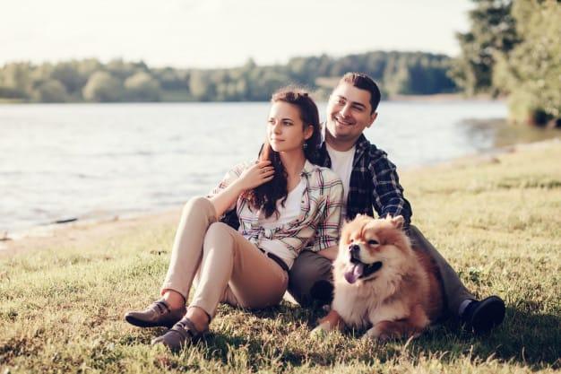 Chow Chow e um casal sentados na grama