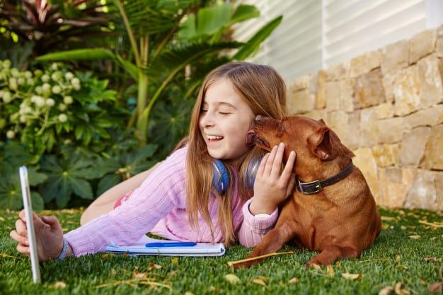 Uma menina e um cachorro deitados no gramado tirando foto