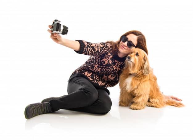 Mulher e um cachorro tirando foto em fundo branco